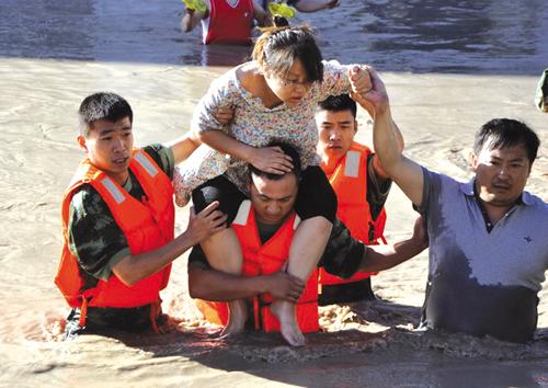 受困孕妇被消防官兵从被淹的房屋内救出。