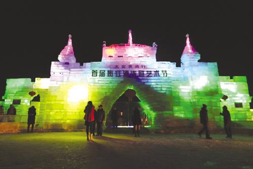 游客在冰雕城堡前留影