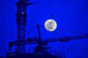 建国门外,工地的塔吊好像将月亮吊了起来。洪辛怡/摄