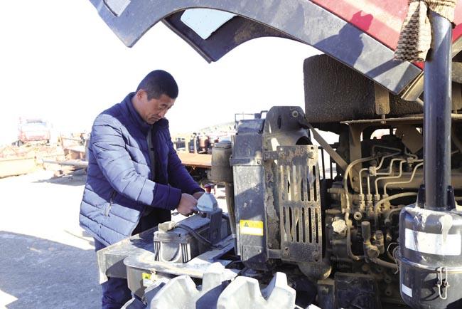通榆县团结铁牛农村合作社农民在修理农机具。