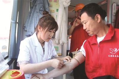 图为志愿者正在进行无偿献血。