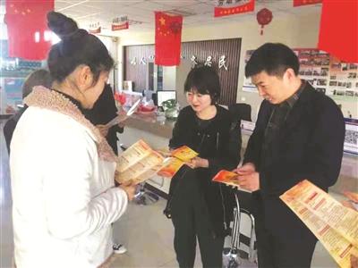 图为工作人员为群众发放宣传手册。