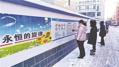 图为居民在帅府小区内浏览宣传板。